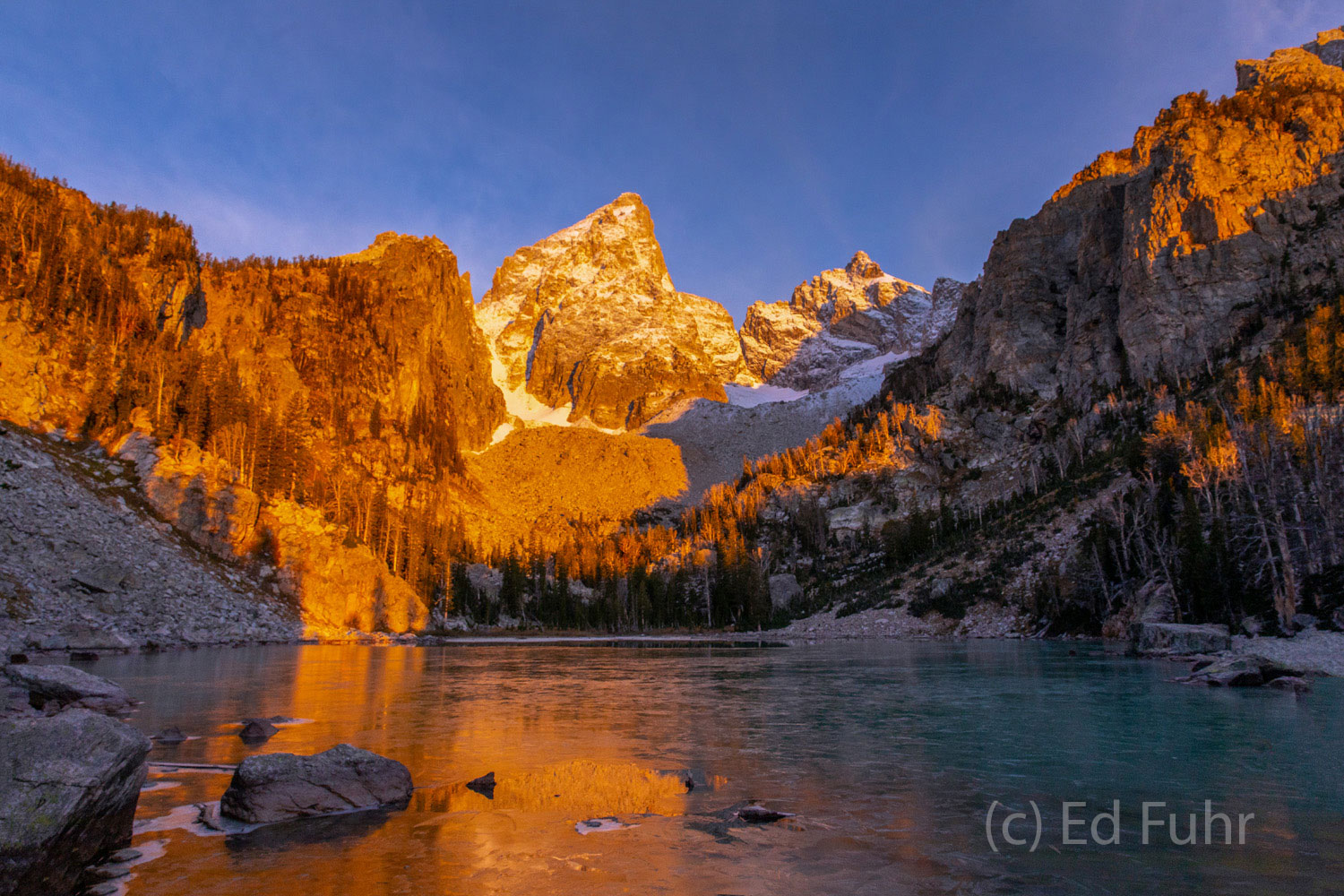 Coated in ice, a high alpine lake reflects the glow or morning's first light, below the peak of the Grand.