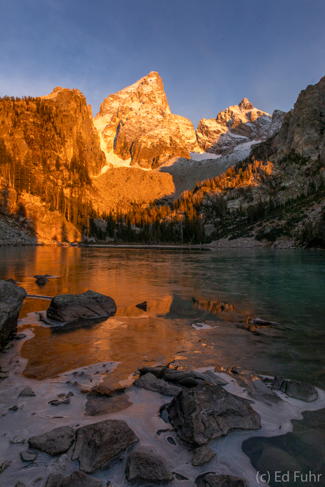 Just below the nearly 14,000 foot peak of the Grand Teton, a high alpine lake is covered at sunrise in a thin layer of ice.