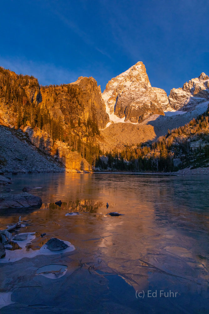 The first snow of mid autumn still clings to the upper reaches of the Grand Teton peak, catching the first warming light of a...