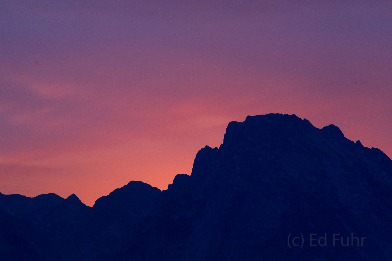 Mount Moran and the northern flank of the Teton range are silhouetted against a colorful evening sky.