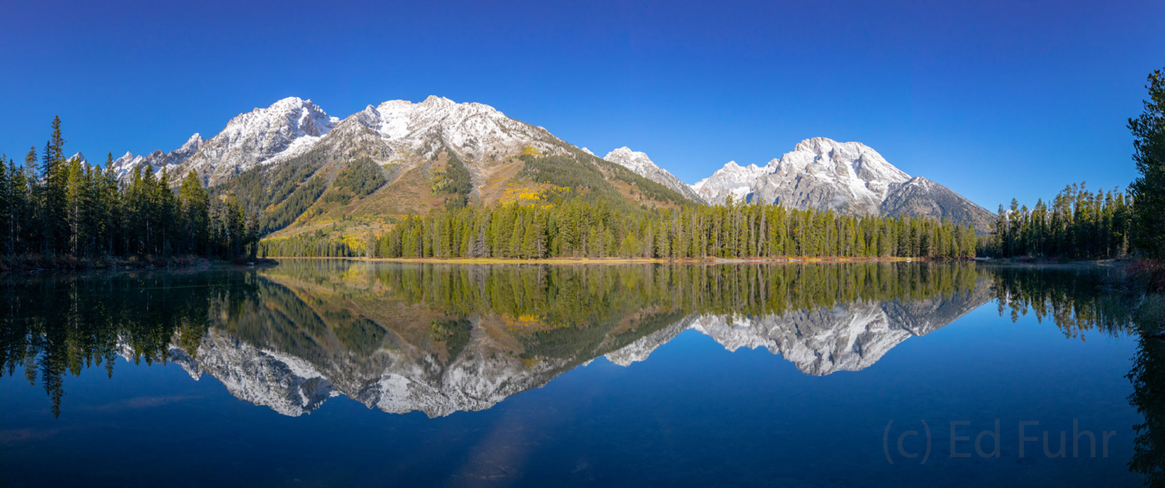 In the perfect stillness of morning, String Lake mirrors the newly coated Teton range, even as pockets of aspen hold on to their...