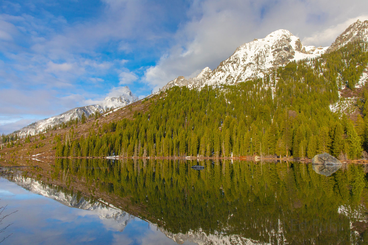 An late spring snow dusts the upper elevations of the Grand Tetons above String Lake.