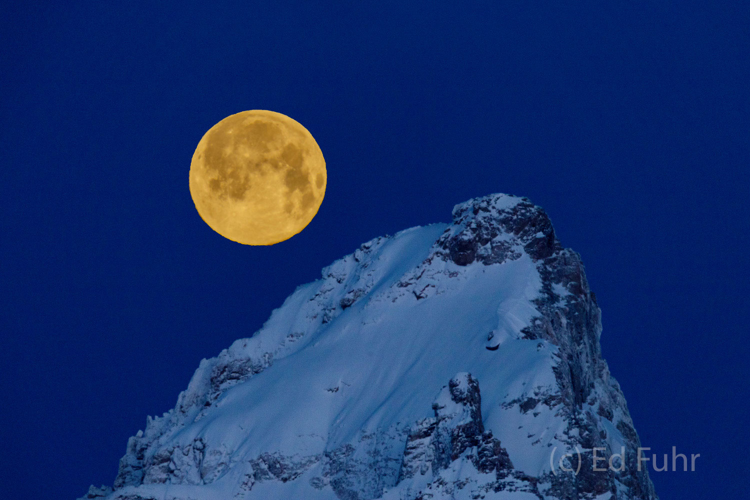 Just before sunrise, the air is crisp and clear.  It is more than 20 below and a super snow moon seems tethered to the Grand...