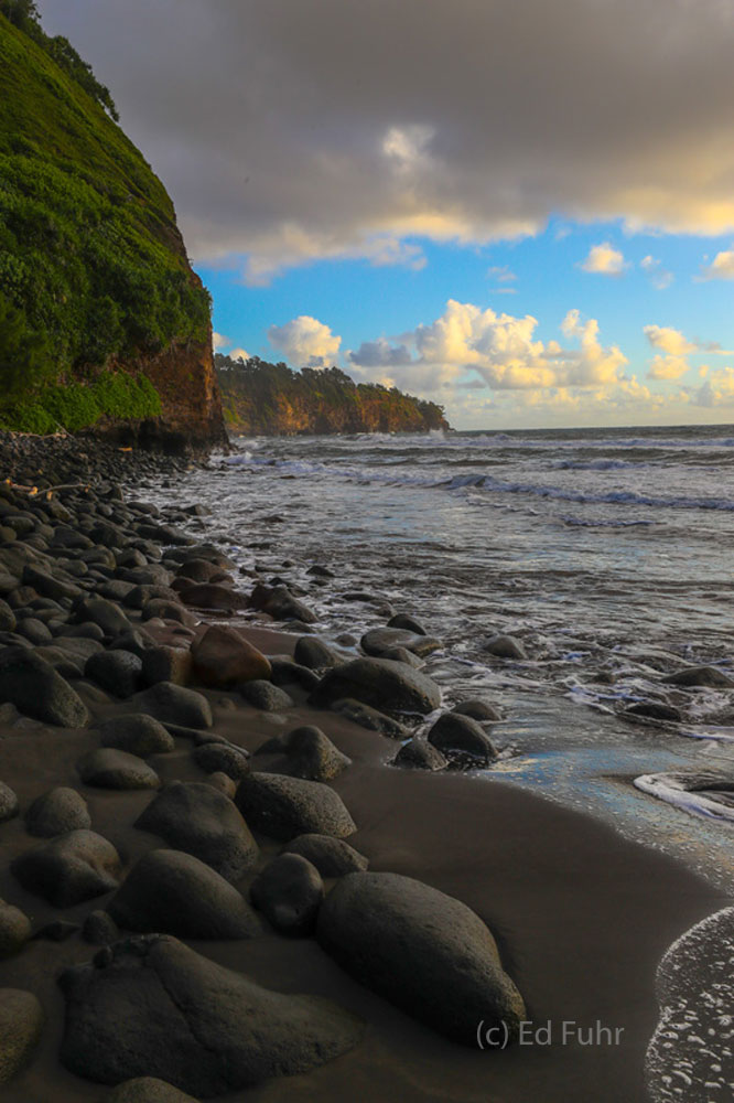 Black lava rocks cover the black sand of the beach by Pololu Valley.