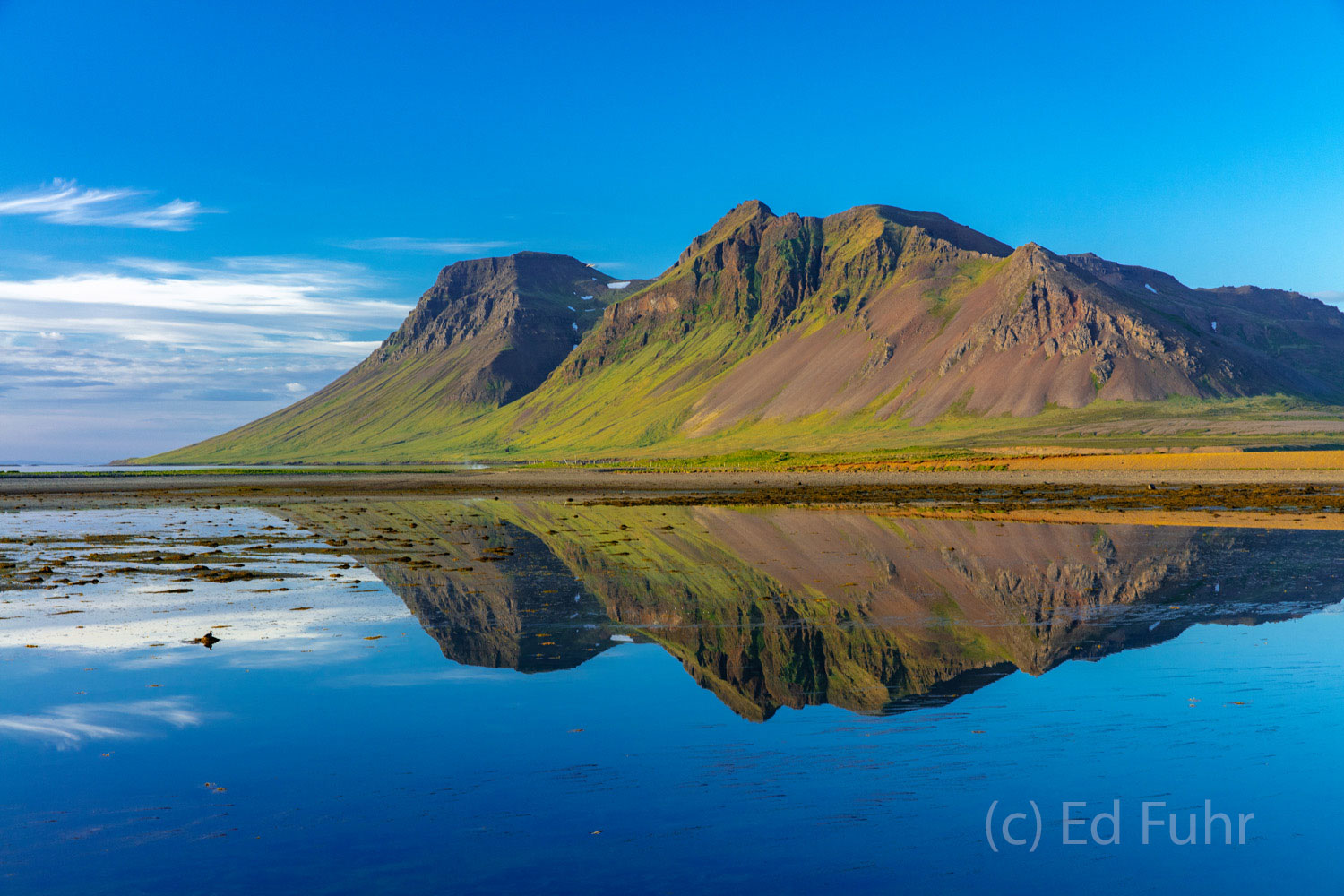 In the late light of day, this small mountain reflects in the nearby bay.