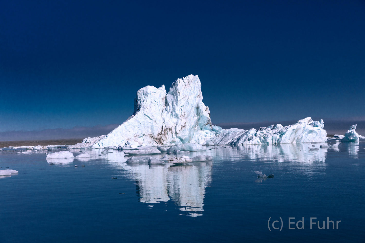 An large iceberg floats in the late afternoon lagoon below the glacier from which it was calved.