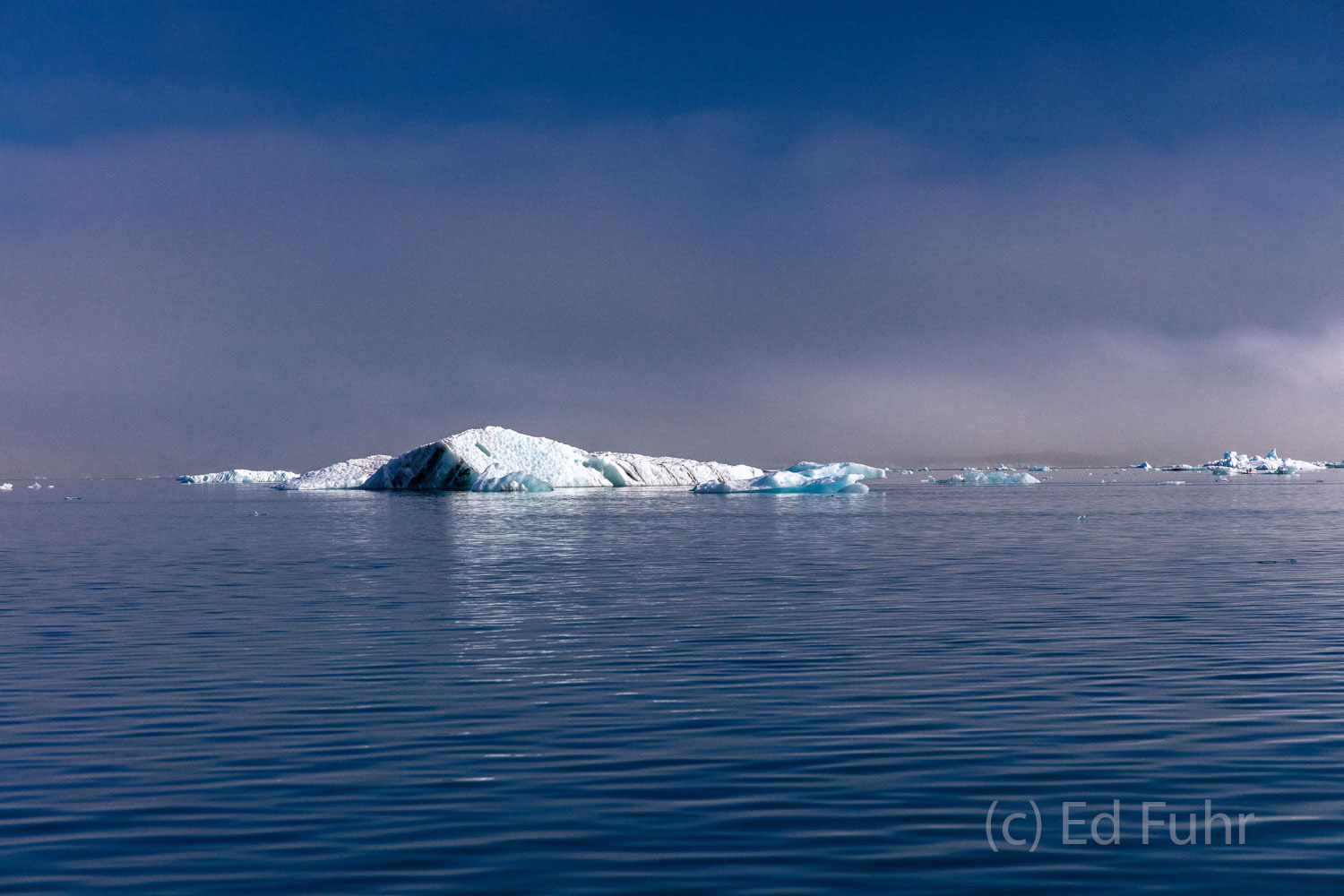 A light fog hovers above this lagoon as a iceberg shimmers in the distance.