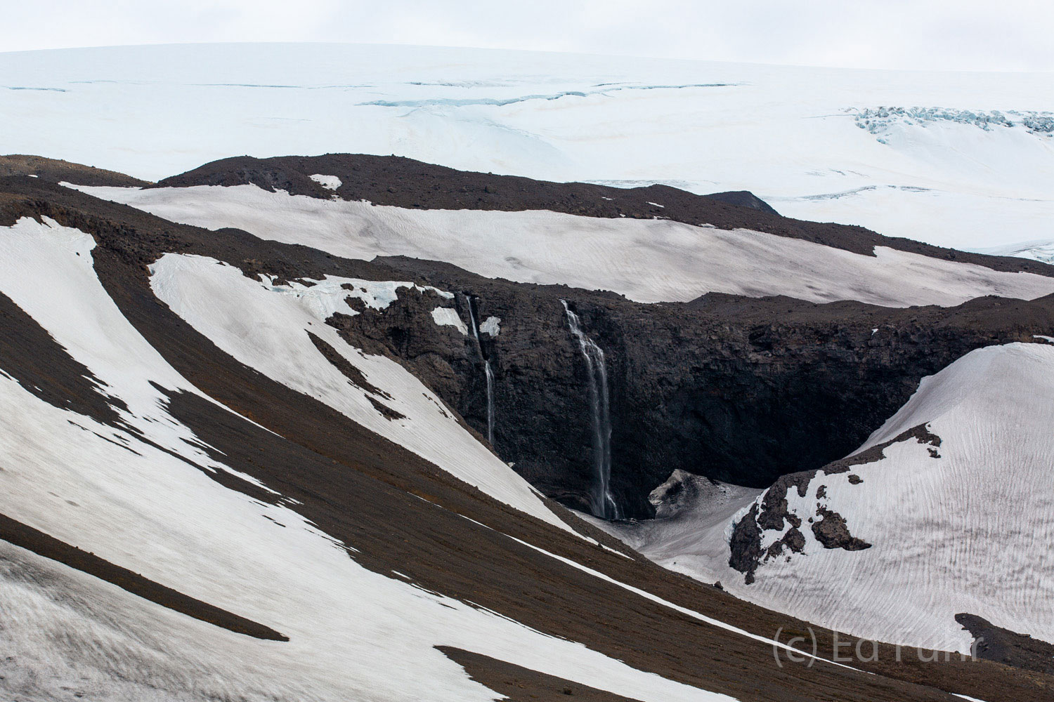 In the center of the island, the glacier Eiriksjokull rises above the cold lava and desolation.