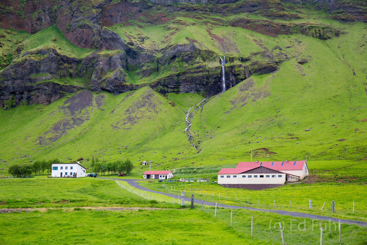 A homestead below an unidentified waterfall, located between its famous sister falls, Skogafoss and Selljalandsfos.