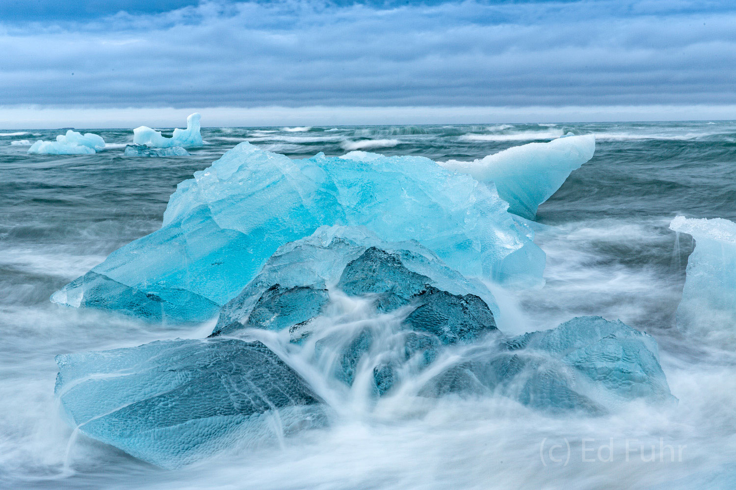 Seemingly defiant, this large blue ice - like some valuable jewel - seems timeless and essential, but the waves and the salt...