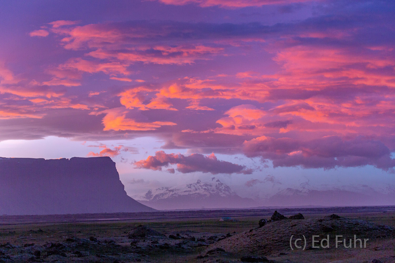 Mount Lomnagur is silhouetted against the pink morning sky above this promontory that juts toward the Ring Road east of Klaustur...