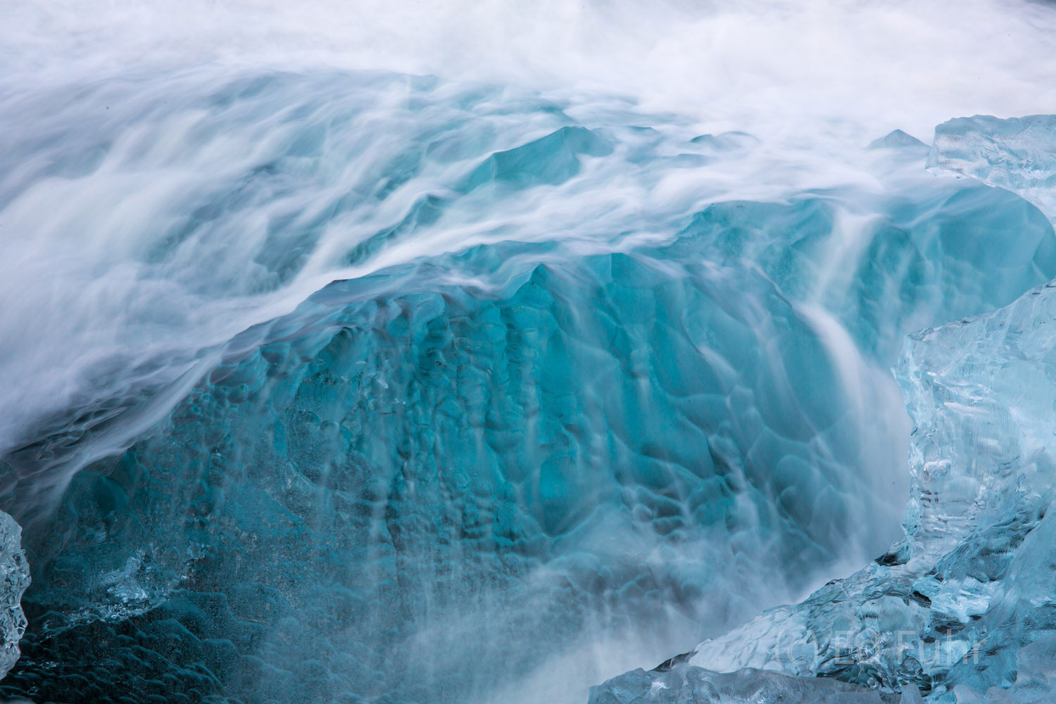 A soft waves cascades over this blue chunk of ice.