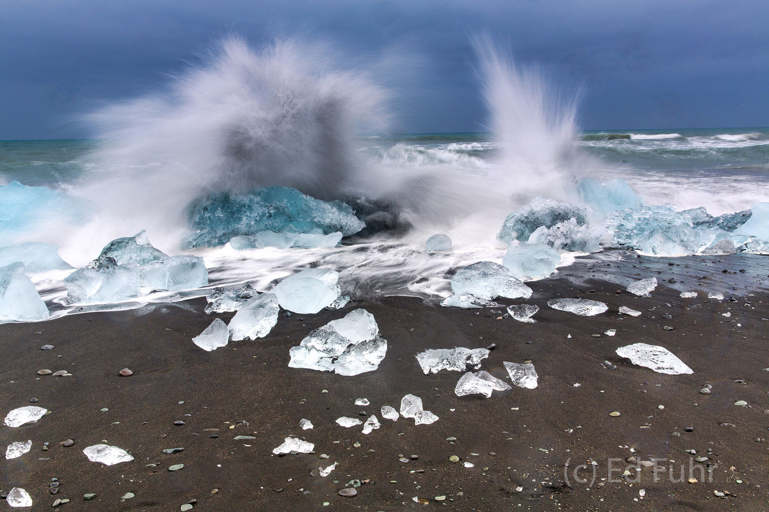 A large wave crashes into an icy boulder orphaned on this black sand beach.