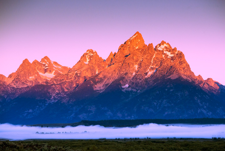 The sun bathes the Teton range above a bank of fog rising above the meandering Snake River that wends its way below.