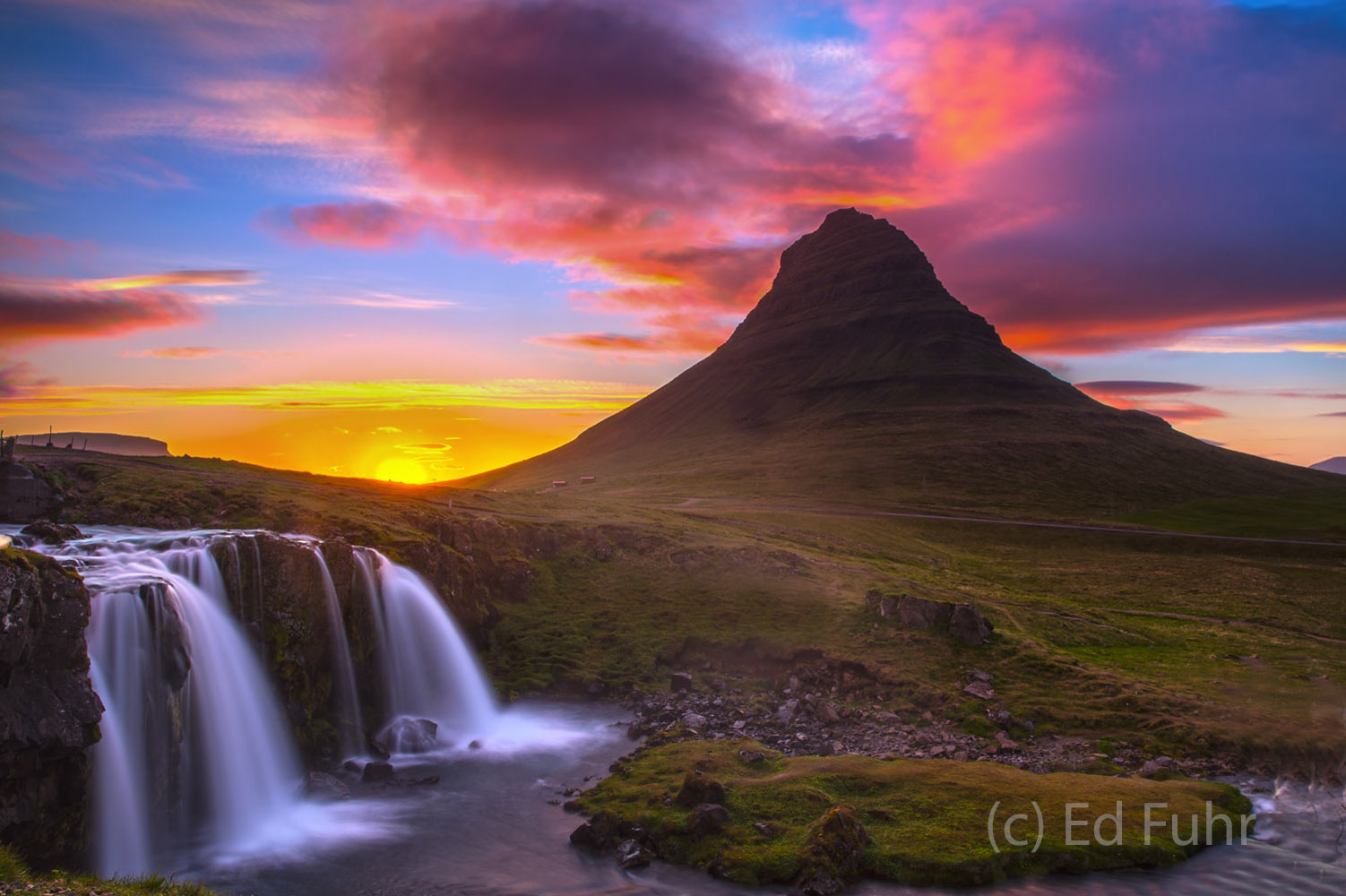 "The midnight sun ""sets"" behind Mt. Kirkjufell only to rise minutes later above the mountains and its waterfall, Kirjufellsfoss..."