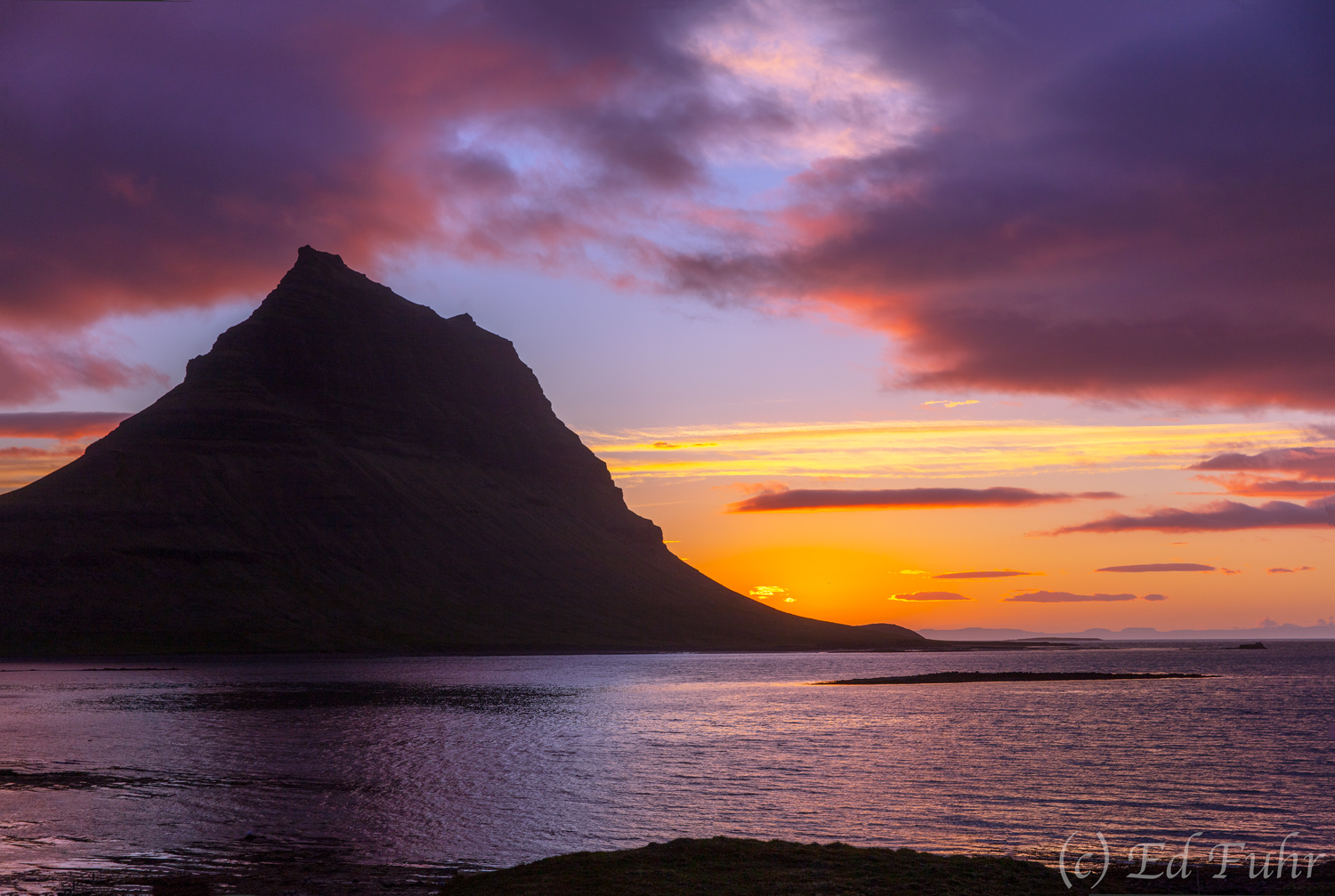 Rising 1519 feet above the sea, Mt. Kirkjufell stands at midnight above the shallow bay that separates Iceland's Snaefellsness...