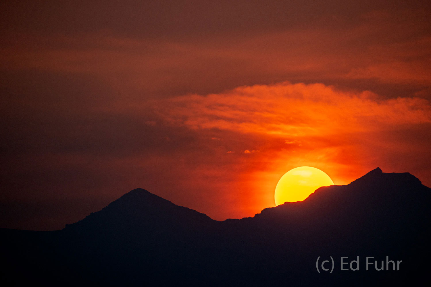 The sun sets over Rendezvous mountain in the Teton Range, through the smoke and haze from California's wildfires