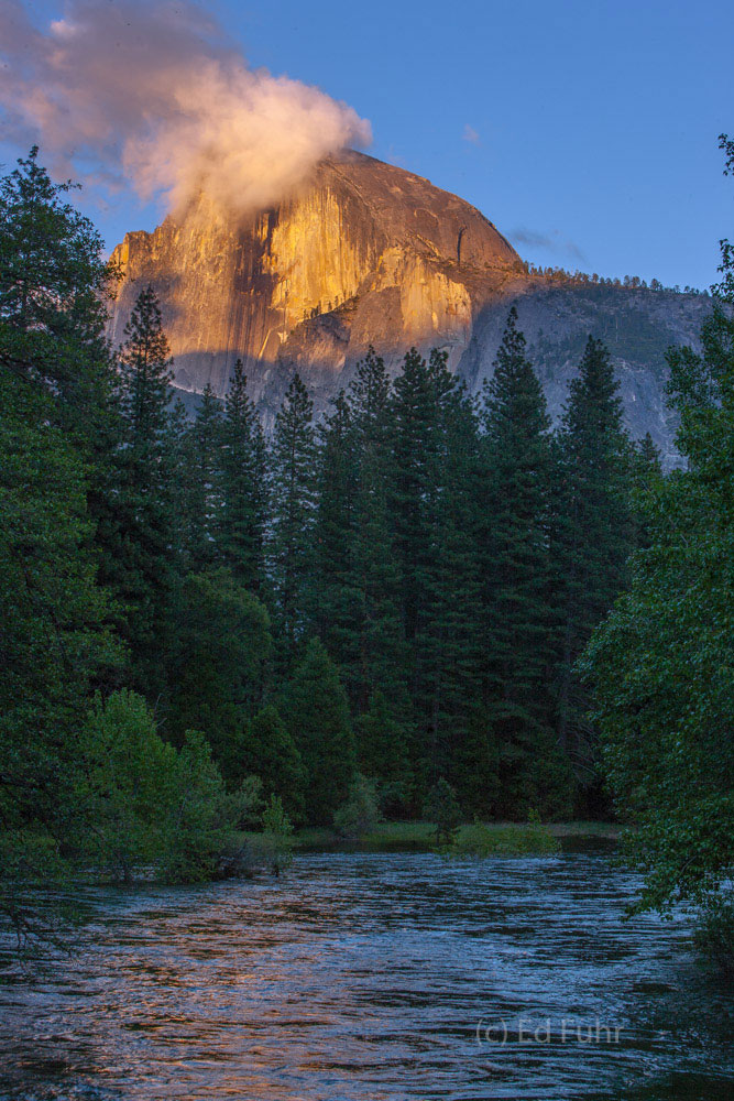 The tip of Half Dome catches the final rays of light above the Merced River.